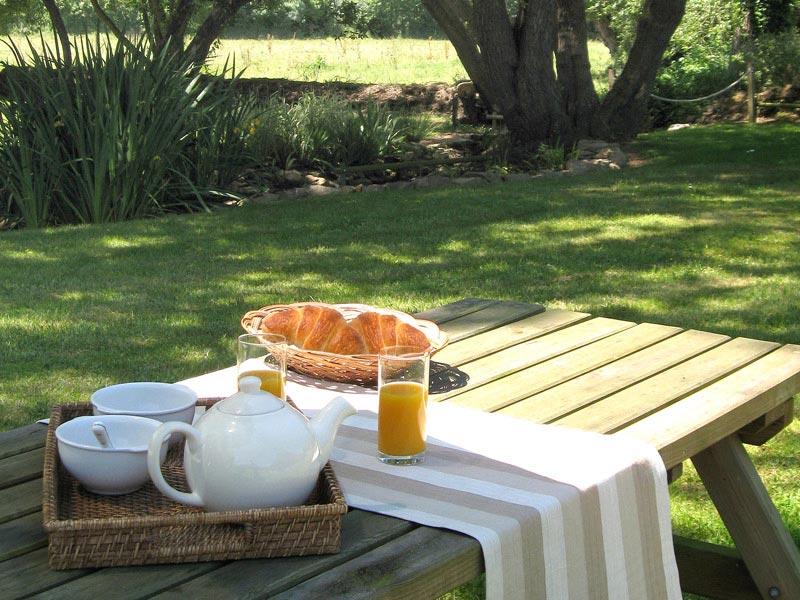 Prendre son petit-déjeuner dans le jardin du gîte © Gite Les 3 Voiles